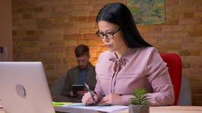 Nahaufnahmetrieb der erwachsenen asiatischen Geschäftsfrau, die an dem Laptop arbeitet und Diagramme zum Geschäftsmannsitzen beha stock footage