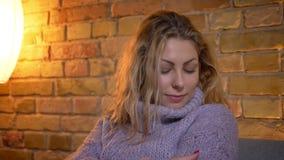 Nahaufnahmetrieb der erwachsenen kaukasischen blonden Frau, die in einer gemütlichen warmen Strickjacke beim auf der Couch zuhaus stock video