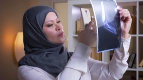 Nahaufnahmetrieb der erwachsenen moslemischen Ärztin im hijab einen Röntgenstrahl glücklich überprüfend und eine Diagnose in best stock video footage