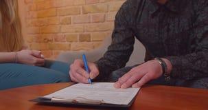 Nahaufnahmetrieb der Frau und des Mannes, die ein Abkommen auf dem Kaufen einer neuen Wohnung machen Männliche Hand, die ein Doku stock footage