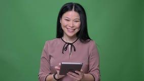 Nahaufnahmetrieb der jungen attraktiven asiatischen Frau mit dem schwarzen Haar, das auf der Tablette mit dem Hintergrund lokalis stock video