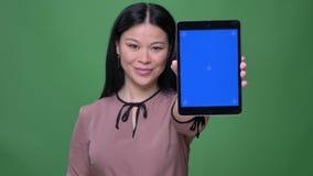 Nahaufnahmetrieb der jungen attraktiven asiatischen Frau mit dem schwarzen Haar unter Verwendung der Tablette und des Zeigens des stock video