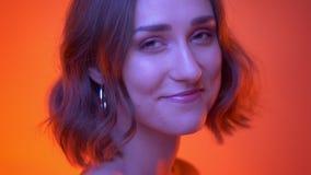 Nahaufnahmetrieb der jungen attraktiven kaukasischen Frau, die an Kamera sich wendet und nett mit rotem Neonhintergrund lächelt stock video footage