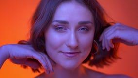 Nahaufnahmetrieb der jungen attraktiven kaukasischen Frau, die mit ihrem Haar betrachtet Kamera mit rotem Neonhintergrund spielt stock video