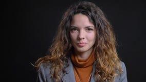 Nahaufnahmetrieb der jungen attraktiven kaukasischen Frau, die seiend schüchtern lächelnd schaut und glücklich mit dem Hintergrun stockfotos
