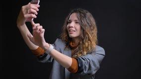 Nahaufnahmetrieb der jungen attraktiven kaukasischen Frau, die selfies am Telefon vor der Kamera mit Hintergrund nimmt stockfotografie