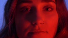 Nahaufnahmetrieb der jungen attraktiven kaukasischen Frau mit dem schönen Make-up, das Kamera mit Neonblauem und rot betrachtet stock video