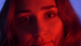 Nahaufnahmetrieb der jungen attraktiven kaukasischen Frau mit schönem Make-up lächelnd Kamera mit Neon glücklich, betrachtend stock video footage