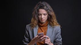 Nahaufnahmetrieb der jungen attraktiven kaukasischen Frau unter Verwendung des Telefons vor der Kamera mit dem Hintergrund an lok lizenzfreies stockbild