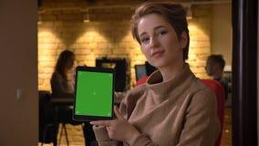 Nahaufnahmetrieb der jungen attraktiven kaukasischen Geschäftsfrau, welche die Tablette verwendet und zuhause grünen Schirm zur K lizenzfreies stockfoto