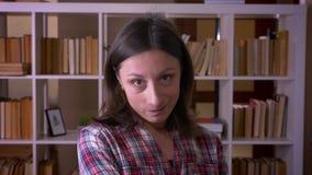 Nahaufnahmetrieb der jungen attraktiven Studentin, die im Vertrauen lächelt, Kamera in der Bibliothek zuhause betrachtend stock video