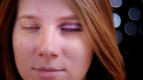 Nahaufnahmetrieb der jungen attraktiven weiblichen Ungedeckthälfte wendete das Make-up an, das gerade Kamera mit bokeh Hintergrun stock footage
