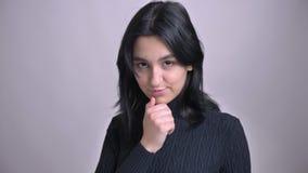 Nahaufnahmetrieb der jungen hübschen kaukasischen Frau, die überzeugt ist und verlockend mit ihrem Haar betrachtet Kamera spielt stock video