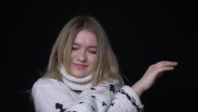 Nahaufnahmetrieb der jungen hübschen kaukasischen Frau in der Strickjacke, die glücklich vor der Kamera mit Hintergrund tanzt stock video footage