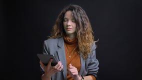 Nahaufnahmetrieb der jungen hübschen kaukasischen Frau unter Verwendung der Tablette mit dem Hintergrund lokalisiert auf Schwarze lizenzfreies stockfoto