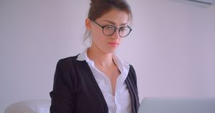 Nahaufnahmetrieb der jungen hübschen kaukasischen Geschäftsfrau, die den Laptop betrachtet die Kamera sitzt im Lehnsessel in verw stock video