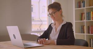 Nahaufnahmetrieb der jungen hübschen kaukasischen Geschäftsfrau, die einen Videoanruf auf dem Laptop nett spricht im Büro hat stock video