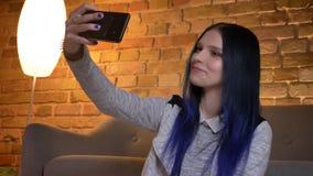 Nahaufnahmetrieb der jungen hübschen kaukasischen Hippie-Jugendlichen, die selfies am Telefon nimmt und in einer gemütlichen Wohn stock video footage