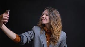 Nahaufnahmetrieb der jungen kaukasischen Frau, die selfies am Telefon nimmt und vor der Kamera mit Hintergrund lächelt stockbilder