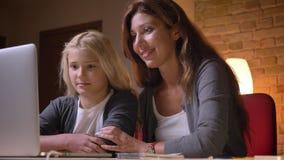 Nahaufnahmetrieb der jungen kaukasischen Mutter und ihrer hübschen der Tochter, die eine lustige Karikatur auf dem Laptop ist auf stock footage