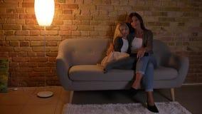 Nahaufnahmetrieb der jungen kaukasischen Mutter und ihrer der Tochter, die im Fernsehen eine Karikatur, aufpasst mit Liebe und Ne stock video footage