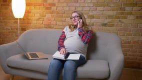 Nahaufnahmetrieb der jungen schwangeren Frau unter Verwendung des Laptops und der nehmen Anmerkungen bei der Unterhaltung am Tele stock video footage