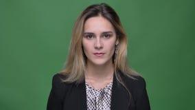 Nahaufnahmetrieb der kaukasischen Frau des jungen attraktiven Hippies, die gerade Kamera mit dem Hintergrund lokalisiert auf Grün stock video footage