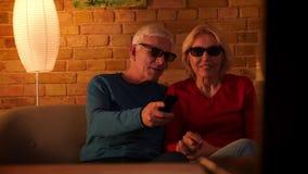 Nahaufnahmetrieb des älteren glücklichen Paars einen Film 3D im Fernsehen, aufpassend auf der Couch in einer gemütlichen Wohnung  stock footage