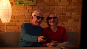 Nahaufnahmetrieb des älteren glücklichen Paars einen Film 3D im Fernsehen, aufpassend auf der Couch nett zuhause sitzen in a zu l stock video footage