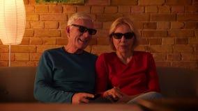 Nahaufnahmetrieb des älteren glücklichen Paars einen Film 3D im Fernsehen, aufpassend Sitzen auf der Couch in einer gemütlichen W stock video footage