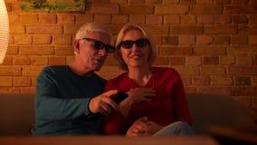 Nahaufnahmetrieb des älteren glücklichen Paars einen Film 3D mit der Freude im Fernsehen aufpassend, die zuhause auf der Couch in stock video footage