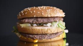 Nahaufnahmetrieb des appetitanregenden doppelten Cheeseburgers mit zwei saftigen Pastetchen und den Würzen stock video