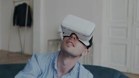 Nahaufnahmetrieb des aufgeregten tausendjährigen Kerls, der das Kopfhörer-Glasgefühl der virtuellen Realität VR vorbei wundernd u stock video footage