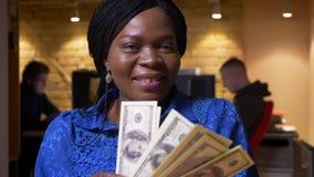 Nahaufnahmetrieb des erfolgreichen erwachsenen Afroamerikanerangestellten, der das Bargeld glücklich lächelt und betrachtet Kamer stock video