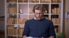 Nahaufnahmetrieb des erwachsenen attraktiven m?nnlichen Studenten, der ein Buch lesend studiert und Kamera in der Universit?tsbib stock video