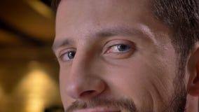 Nahaufnahmetrieb des erwachsenen kaukasischen bärtigen männlichen Gesichtes mit den Augen, die zuhause Kamera mit lächelndem Gesi stockfoto