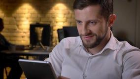 Nahaufnahmetrieb des erwachsenen kaukasischen Geschäftsmannes, der auf der Tablette simst und nett zuhause auf dem Arbeitsplatz h stockbild