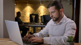 Nahaufnahmetrieb des erwachsenen kaukasischen Geschäftsmannes, der zuhause auf dem Laptop im Büro schreibt lizenzfreie stockbilder
