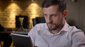 Nahaufnahmetrieb des erwachsenen kaukasischen Geschäftsmannes, der zuhause auf der Tablette auf dem Arbeitsplatz im Büro simst lizenzfreies stockbild