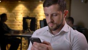 Nahaufnahmetrieb des erwachsenen kaukasischen Geschäftsmannes, der zuhause am Telefon auf dem Arbeitsplatz im Büro grast lizenzfreie stockfotos