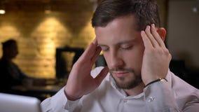 Nahaufnahmetrieb des erwachsenen kaukasischen männlichen Angestellten, der Kopfschmerzen und ein beind hat, betonte und verwüstet lizenzfreie stockfotos