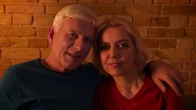 Nahaufnahmetrieb des gealterten glücklichen Paars, das fernsieht, mit der Aufregung zu lächeln zuhause sitzt auf der Couch in ein stock video