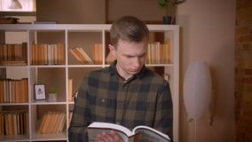 Nahaufnahmetrieb des jungen attraktiven kaukasischen männlichen Studenten, der ein Buch lesend lernt und Kamera im College betrac stock video