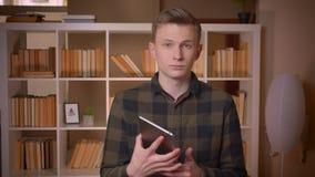 Nahaufnahmetrieb des jungen attraktiven kaukasischen männlichen Studenten unter Verwendung der Tablette und des Zeigens des blaue stock footage