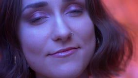 Nahaufnahmetrieb des jungen attraktiven kaukasischen weiblichen Gesichtes, das Kamera mit glücklichem Gesichtsausdruck mit Neonro stock video footage