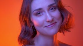 Nahaufnahmetrieb des jungen attraktiven kaukasischen weiblichen Gesichtes, das lächelt Kamera mit rotem Neonhintergrund glücklich stock video