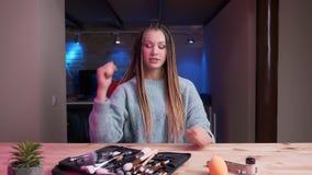 Nahaufnahmetrieb des jungen attraktiven weiblichen Maskenbildners mit dem Dreadlocksströmen Live und der Werbung von Kosmetik mit stock footage