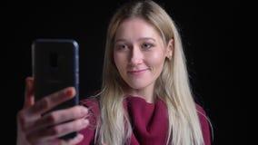 Nahaufnahmetrieb des jungen hübschen kaukasischen Mädchens mit dem langen blonden Haar, das ein lächelndes wellenartig bewegendes stock footage