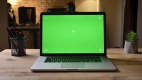 Nahaufnahmetrieb des Laptops mit grünem Schirm auf dem Schreibtisch im Büro, welches zuhause die Arbeitsplatzorganisation gefan stock video footage
