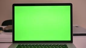 Nahaufnahmetrieb des Schlüsselschirmes der grünen Farbenreinheit des Computers, der zuhause auf dem Schreibtisch im Büro liegt stock footage